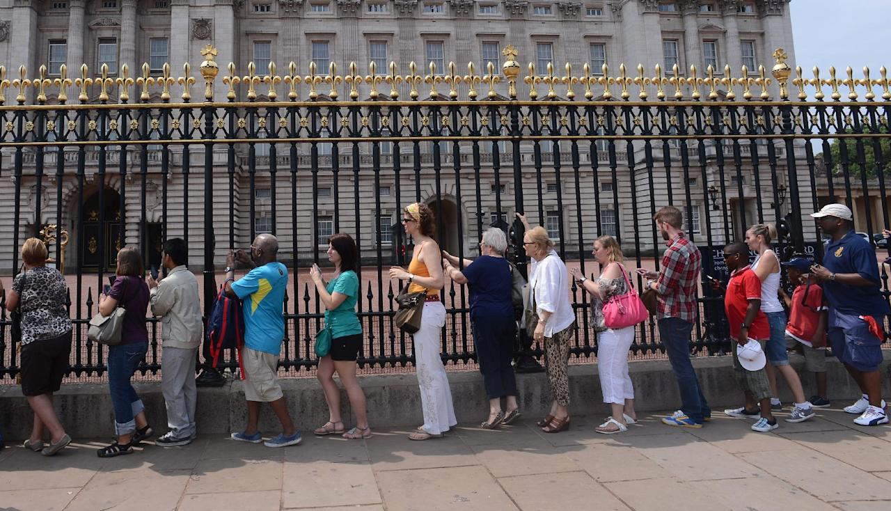 Members of the public queuing to look at the official announcement that the Duke and Duchess of Cambridge have had a baby boy, outside Buckingham Palace in London.