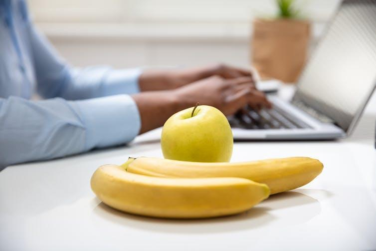 A close-up of an apple and two bananas on an office desk.