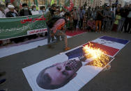 Pakistani Shiite Muslims burn a representation of a French flag and a defaced image of French President Emmanuel Macron during a rally against the French president and the republishing of caricatures of the Prophet Muhammad they deem blasphemous, near the French consulate in Karachi, Pakistan, Sunday, Nov. 1, 2020. (AP Photo/Fareed Khan)