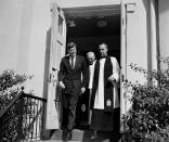 FILE - In this March 10, 1963 file photo, President John F. Kennedy leaves St. John's Episcopal Church after attending Mass at St. Stephens Roman Catholic Church in Washington. At right is Rev. John C. Harper, new rector of the church, and at rear is the Right Rev. William F. Creighton, Episcopal Bishop of Washington. During his visit to St. John's, Kennedy signed a prayer book which bears the signatures of all presidents since Herbert Hoover. (AP Photo)