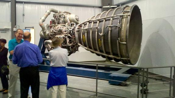 A California Science Center guide discusses the Space Shuttle Main Engine display with invited guests.