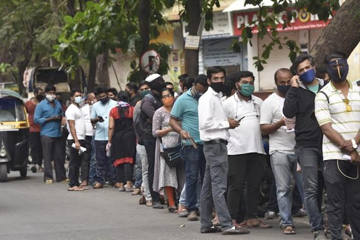 People wait in queues outside the office of the Chemists Association to demand necessary supply of the anti-viral drug Remdesivir, in Pune, India, Thursday, April 8, 2021. India is experiencing its worst pandemic surge, with a seven-day rolling average of more than 130,000 cases per day. Hospitals across the country are starting to get overwhelmed with patients, and experts worry the worst is yet to come. (AP Photo)