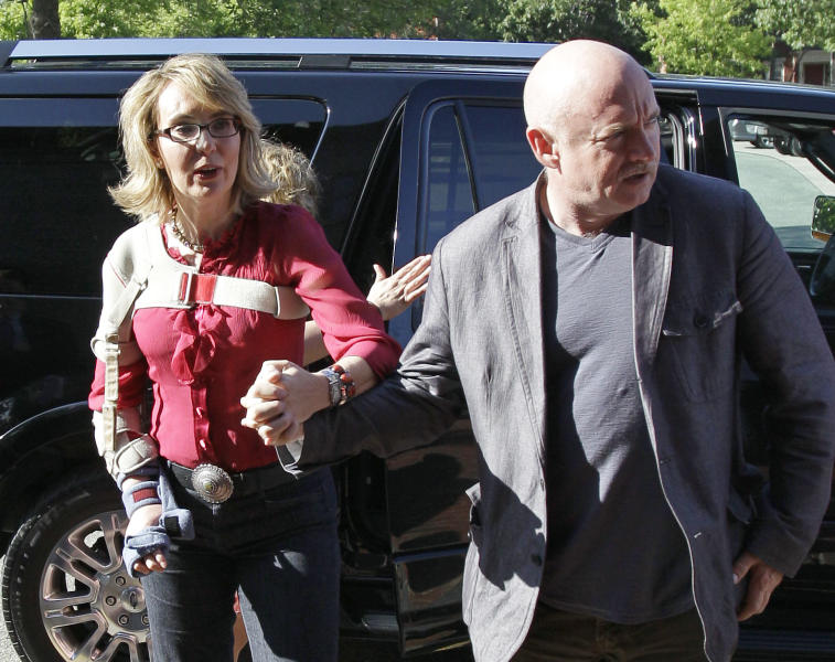 In this photo taken Friday, July 5, 2013, former Arizona Rep. Gabrielle Giffords and her husband, retired astronaut and combat veteran Capt. Mark Kelly, arrive to meet with local supporters and parents of Sandy Hook Elementary School victims at the Orchard Street Chop Shop in Dover, N.H. Three years after being shot in the head, Giffords is in New Hampshire to urge support for background checks on gun purchases. (AP Photo/Mary Schwalm)