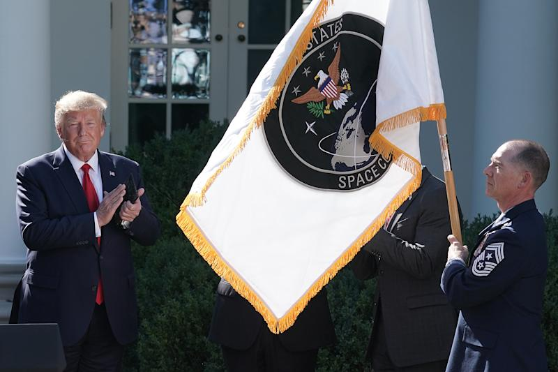 WASHINGTON, DC - AUGUST 29: U.S. President Donald Trump (L) applauds as the flag for the new the U.S. Space Command is revealed in the Rose Garden at the White House August 29, 2019 in Washington, DC. Citing potential threats from China and Russia and the nation's reliance on satellites for defense operations, Trump said the U.S. needs to launch a 'space force.' U.S. Air Force Gen. John Raymond will serve as the first head of Space Command, which will have 87 active units handling operations such as missile warning, satellite surveillance, space control and space support. (Photo by Chip Somodevilla/Getty Images)