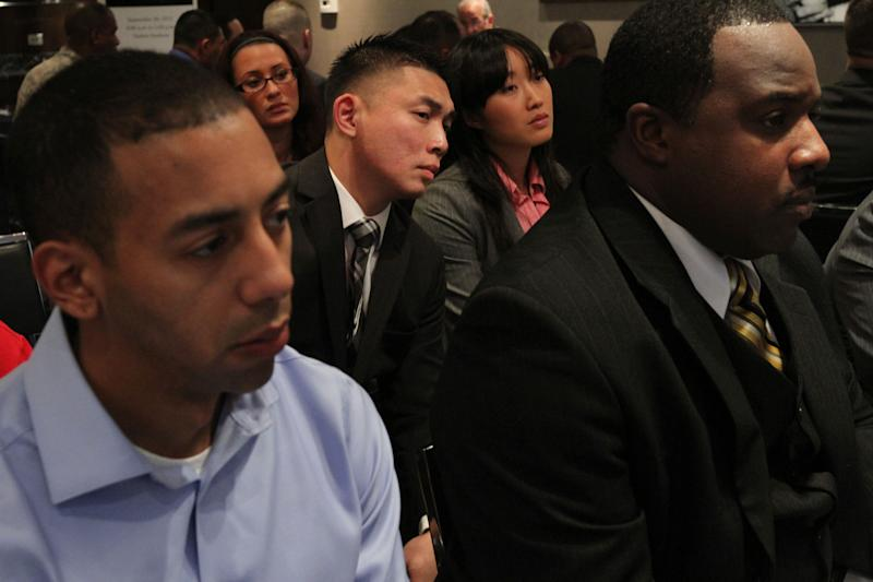 In this Friday Sept. 28, 2012, photo, a group of veterans listen during a session with one of the employers at a job fair introducing veterans to careers in the security and private investigations industry at Yankee Stadium in the Bronx borough of New York.  The number of Americans seeking unemployment aid plummeted the week of Oct. 4, 2012, to seasonally adjusted 339,000, the lowest level in more than four years. The sharp drop offered a hopeful sign that the job market could pick up. (AP Photo/Tina Fineberg)