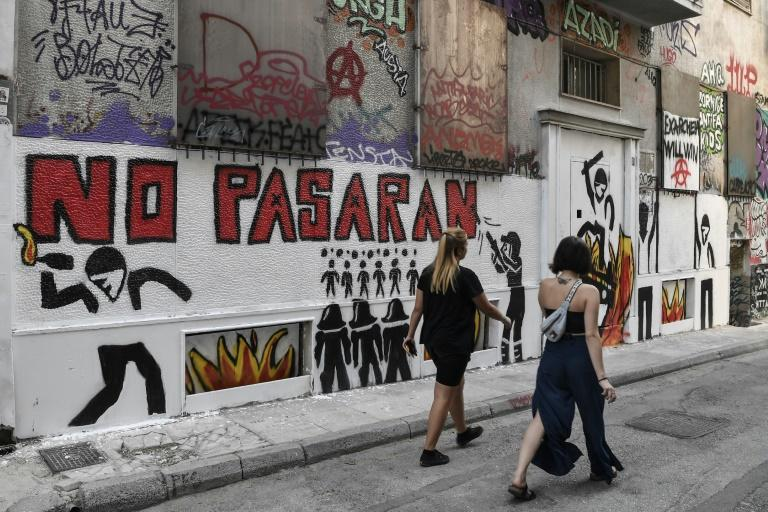 Women walk past a recent graffiti in Athens' historic district of Exarchia