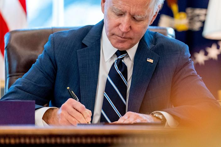 President Joe Biden signs the American Rescue Plan, a coronavirus relief package, in the Oval Office of the White House, Thursday, March 11, 2021, in Washington.