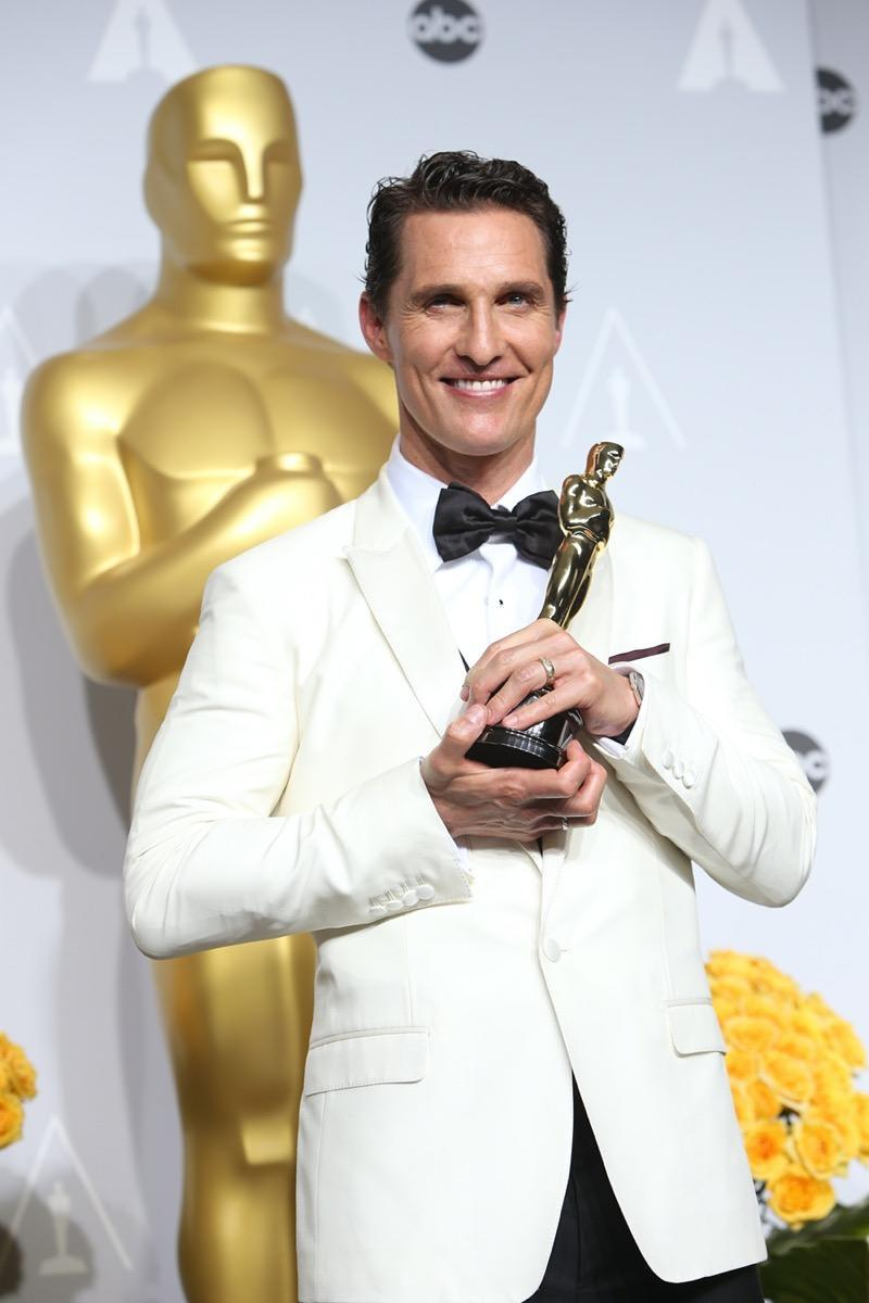 matthew mcconaughey in a white suit holding an oscar