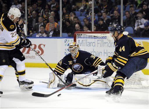 Boston Bruins left winger Shawn Thornton (22) battles for a rebound with Buffalo Sabres goaltender Ryan Miller (30) and defenseman Andrej Sekera (44), of Slovakia, during the second period of an NHL hockey game in Buffalo, N.Y., Sunday, March 31, 2013. (AP Photo/Gary Wiepert)