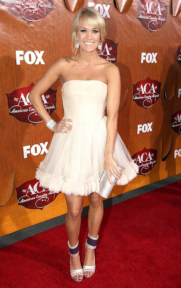 Country crooner Carrie Underwood showed off her toned gams in a strapless, above-the-knee frock as she walked the red carpet for the American Country Awards at the MGM Garden Arena in Las Vegas on Monday. The songstress was up for Artist of the Year: Female and a trio of other honors at the ceremony. But whether she wins or loses, the real question is ... what do you think of that dress? (12/05/2011)