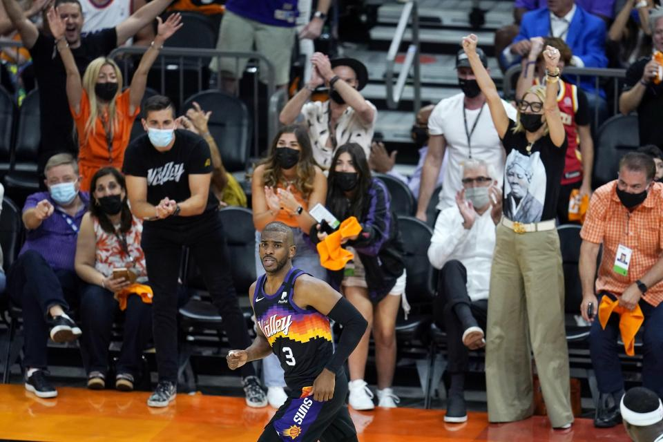 Phoenix Suns fans cheer on Suns guard Chris Paul (3) after he made a 3-pointer against the Milwaukee Bucks during the second half of Game 1 of basketball's NBA Finals, Tuesday, July 6, 2021, in Phoenix. (AP Photo/Ross D. Franklin)