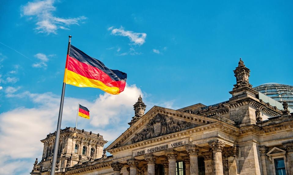 German flags waving in the wind at famous Reichstag building, seat of the German Parliament Deutscher Bundestag , on a sunny day with blue sky and clouds, central Berlin Mitte district, Germany