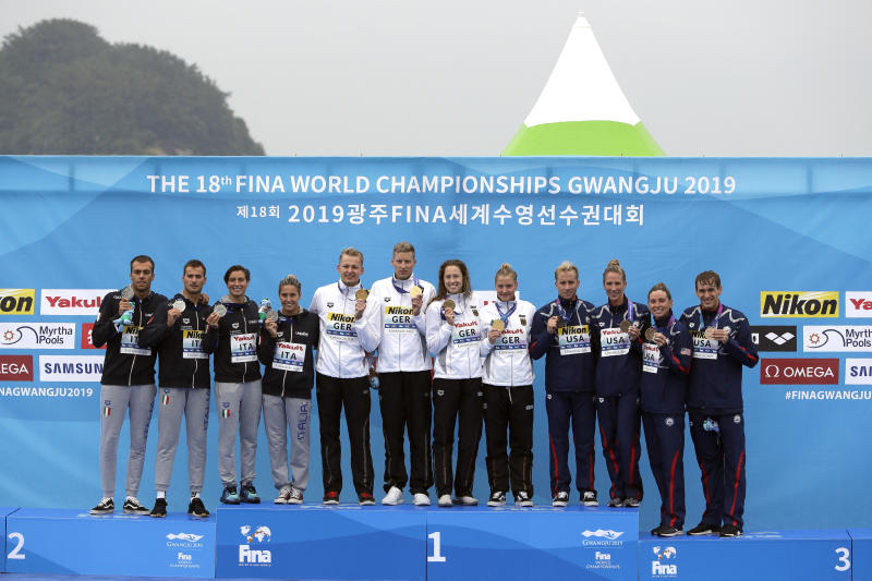 From left, the silver medal team from Italy, the gold medal team from Germany, and the bronze medal team from the United States stand on the podium after the 5km mixed relay open water swim at the World Swimming Championships in Yeosu, South Korea, Thursday, July 18, 2019. (AP Photo/Mark Schiefelbein)