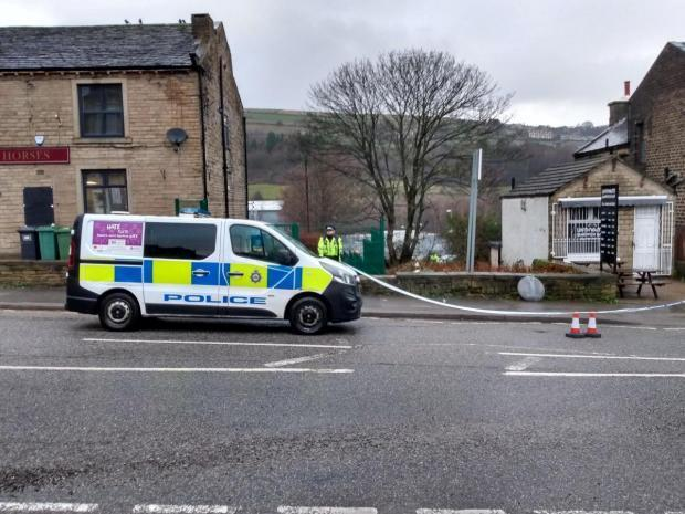 Police on the scene at Manchester Road in Linthwaite, Huddersfield, where a factory worker has died and another man was seriously injured when they were stabbed during a confrontation outside a pharmaceutical plant (Picture: SWNS)