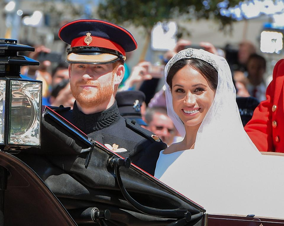 WINDSOR, ENGLAND - MAY 19:  (L-R) Prince Harry, Duke of Sussex and Meghan, Duchess of Sussex leave Windsor Castle in the Ascot Landau carriage during a procession after getting married at St Georges Chapel on May 19, 2018 in Windsor, England. Prince Henry Charles Albert David of Wales marries Ms. Meghan Markle in a service at St George's Chapel inside the grounds of Windsor Castle. Among the guests were 2200 members of the public, the royal family and Ms. Markle's mother, Doria Ragland.  (Photo by George Pimentel/WireImage)