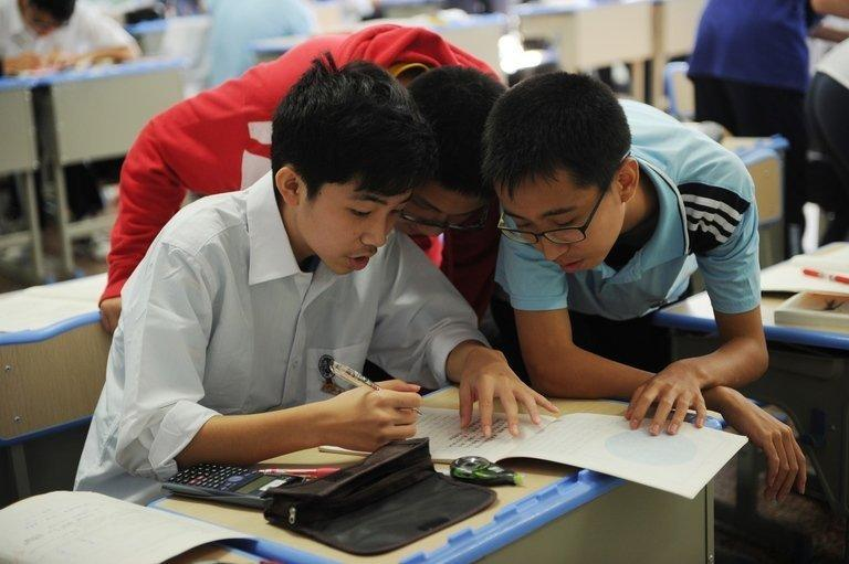 Boys solve a maths problem at the government-run Number Eight High School in Shanghai, on October 15, 2012
