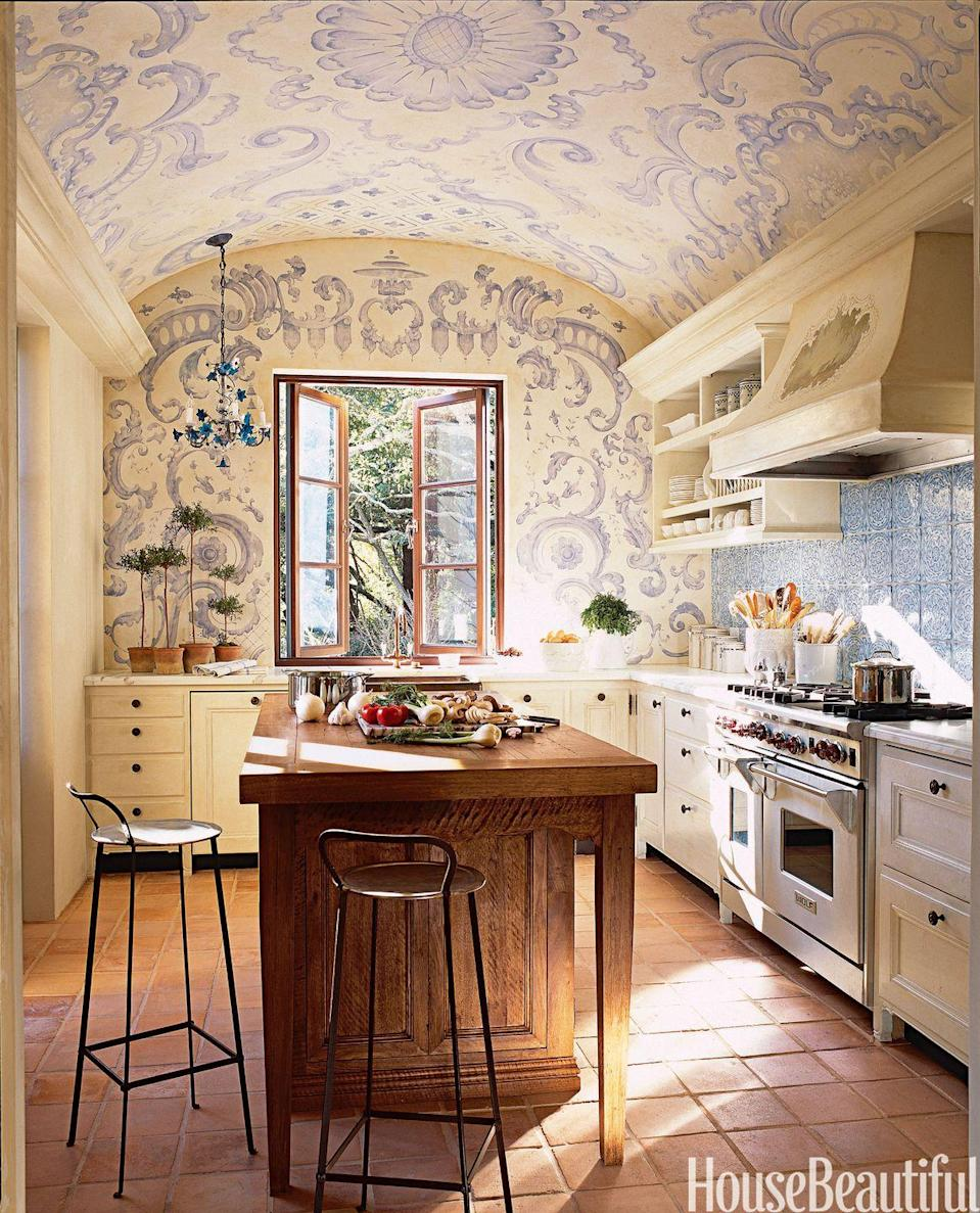 "<p>Architecture and ornamental wall detailing make this kitchen <span class=""redactor-unlink"">whimsical—</span>and just a touch dramatic. The lavender swirls of paint on a buttercream backdrop complement the elaborate blue chandelier, too. Then the classic, neutral cabinets and island ground the space. </p>"
