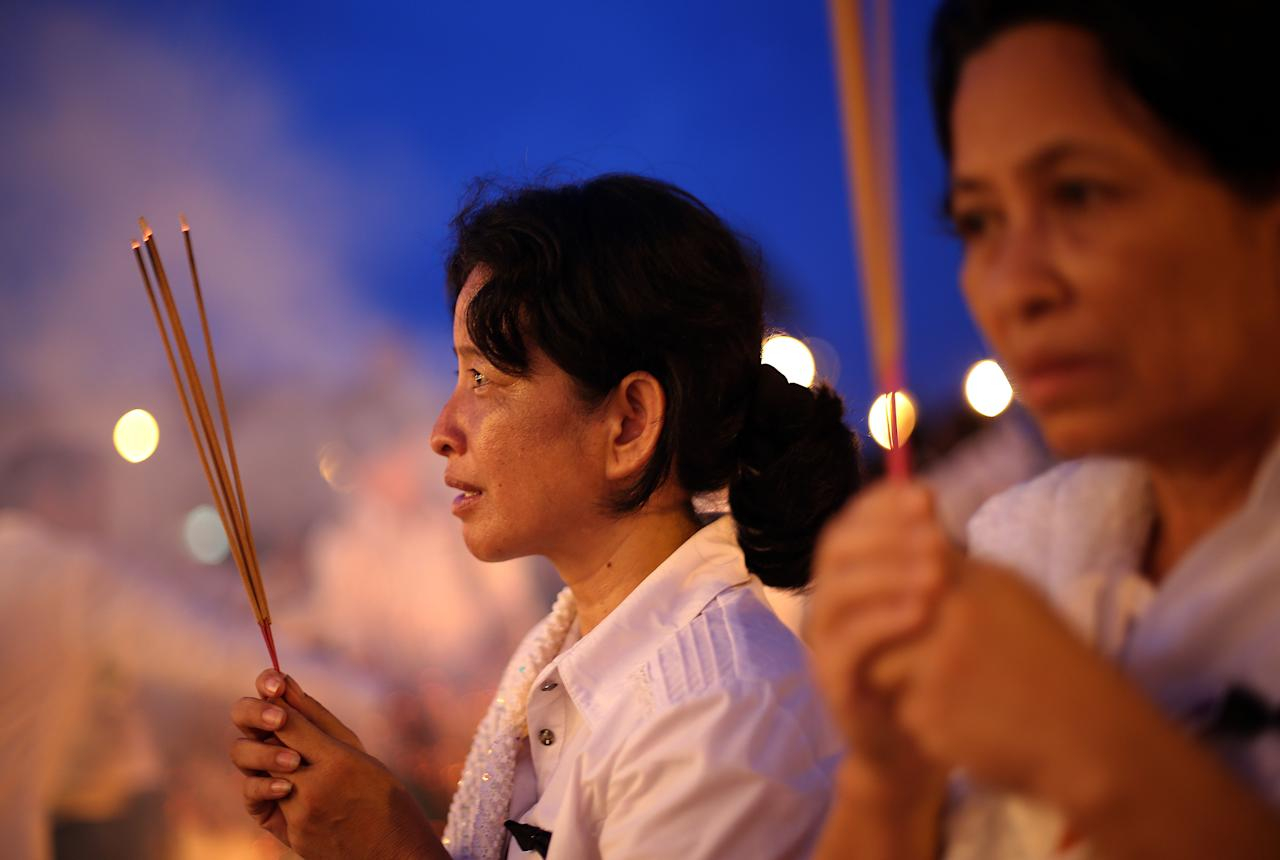 Mourners burn incense and offer prayers at the Royal Palace as the body of King Norodom Sihanouk returned in Phnom Penh, Cambodia, Wednesday Oct. 17, 2012. The body of Cambodia's late King Norodom Sihanouk returned to his homeland on a plane from China on Wednesday, welcomed by tens of thousands of mourners who packed tree-lined roads in the Southeast Asian nation's capital ahead of the royal funeral. (AP Photo/Wong Maye-E)