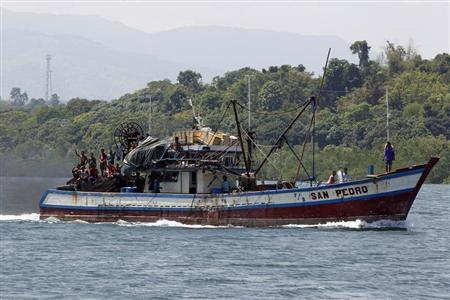 Filipino fishermen wave from a fishing boat bound to fish near Scarborough Shoal in Masinloc