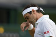 Switzerland's Roger Federer wipes his brow during the men's singles quarterfinals match against Poland's Hubert Hurkacz on day nine of the Wimbledon Tennis Championships in London, Wednesday, July 7, 2021. (AP Photo/Kirsty Wigglesworth)