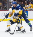 Vancouver Canucks defenseman Quinn Hughes (43) fights for control of the puck with Nashville Predators center Craig Smith (15) during the second period of an NHL hockey game Tuesday, Nov. 12, 2019, in Vancouver, British Columbia. (Jonathan Hayward/The Canadian Press via AP)