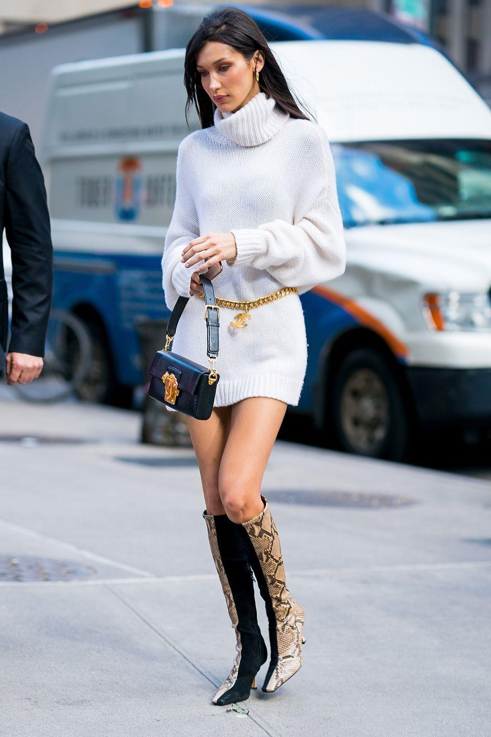 <p>Hadid wore a pair of Céline python print boots, a Dolce & Gabbana Lucia lizard-effect black leather shoulder bag, Chanel classic Jumbo logo chain, a pair of Luv Aj Baby Amalfi tube hoops in gold with a Denim BF cashmere turtleneck dress-sweater, November 2018.</p>