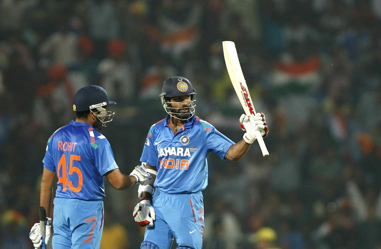 Rohit Sharma congratulates Shikhar Dhawan as he lifts his bat after completing half century during the 6th ODI between India and Australia Vidarbha Cricket Association Stadium, Jamtha in Nagpur on Oct.30, 2013. (Photo: IANS)