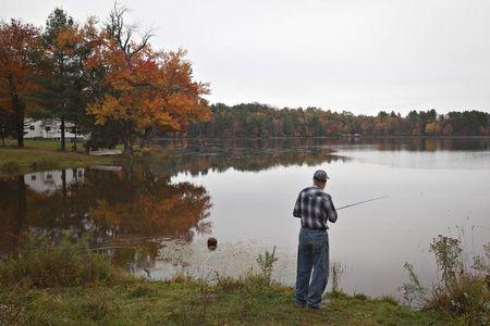 With the fall colors reflected in a lake, a man fishes for bass as it rains in Jeffersonville, New York