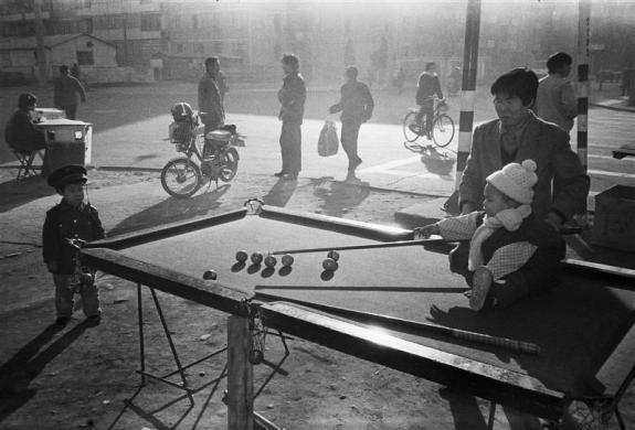 A child sitting on a roadside snooker pool plays with her mother in Beijing in 1983.