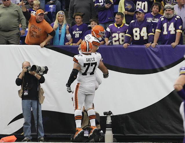 Cleveland Browns tight end Jordan Cameron, top, celebrates with teammate John Greco (77) after catching a 7-yard touchdown pass during the second half of an NFL football game against the Minnesota Vikings Sunday, Sept. 22, 2013, in Minneapolis. The Browns won 31-27. (AP Photo/Ann Heisenfelt)