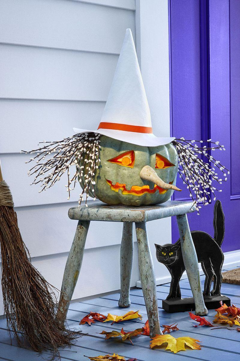 "<p>Make this bewitching display at home by first hollowing a green heirloom pumpkin. Carve out mouth and eyes, then attach parsnip nose with toothpicks. Straight-pin faux berry branches on top for hair. <a href=""https://www.womansday.com/home/crafts-projects/g3200/halloween-2017-templates/"" rel=""nofollow noopener"" target=""_blank"" data-ylk=""slk:Print hat template"" class=""link rapid-noclick-resp"">Print hat template</a> and trace onto felt; cut out tracing and assemble with hot glue. Wrap ½-inch satin ribbon above hat brim and place on top of hair.</p>"