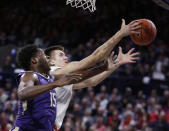 Washington forward Noah Dickerson (15) and Gonzaga forward Filip Petrusev go after a rebound during the first half of an NCAA college basketball game in Spokane, Wash., Wednesday, Dec. 5, 2018. (AP Photo/Young Kwak)