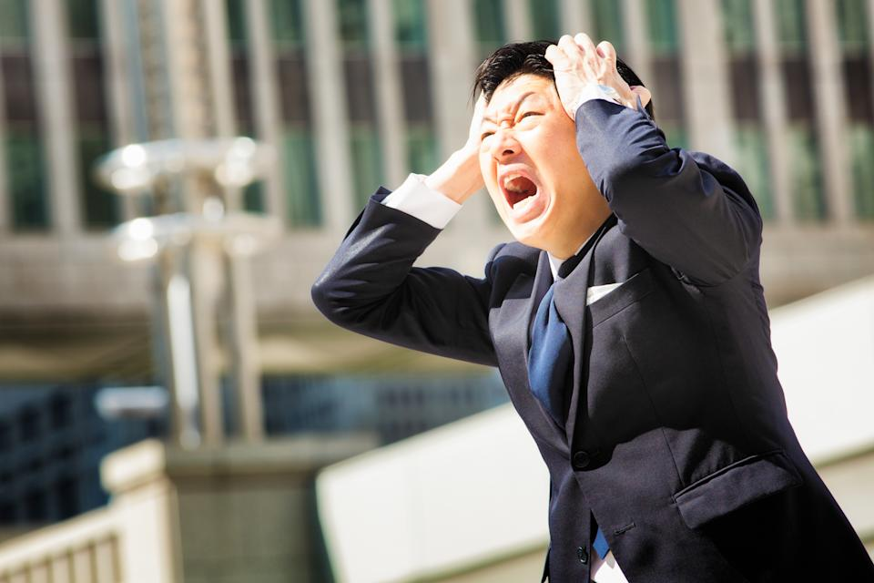 Furious angry Japanese office worker screams in despair while holding his head with both hands. Office building in the background. Photographed in Shinjuku, Tokyo, Japan.