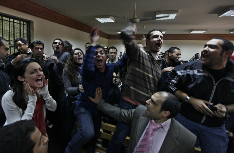 FILE - In this Sunday, Feb. 26, 2012 file photo, Egyptian protesters chant anti-military ruling slogans during a trial of employees of pro-democracy groups charged with using foreign funds to foment unrest in Cairo, Egypt. Egypt has lifted a travel ban on Wednesday, Feb. 29 for seven Americans charged with fomenting unrest by working for illegally funded pro-democracy groups, signaling an end to the worst crisis in Egypt-U.S. relations in 30 years. (AP Photo/Khalil Hamra, File)