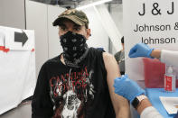 FILE - In this July 30, 2021, file photo, Jay Vojno gets the Johnson & Johnson COVID-19 vaccine, in New York. In both the U.S. and the EU, officials are struggling with the same question: how to boost vaccination rates to the max and end a pandemic that has repeatedly thwarted efforts to control it. In the United States, President Joe Biden has issued sweeping vaccine mandates. (AP Photo/Mark Lennihan, File)