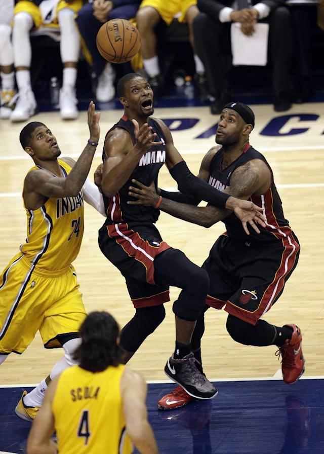 Indiana Pacers forward Paul George, left, and Miami Heat's Chris Bosh, center and LeBron James compete for a rebound during the first half of Game 2 of the NBA basketball Eastern Conference finals in Indianapolis, Tuesday, May 20, 2014. (AP Photo/AJ Mast)
