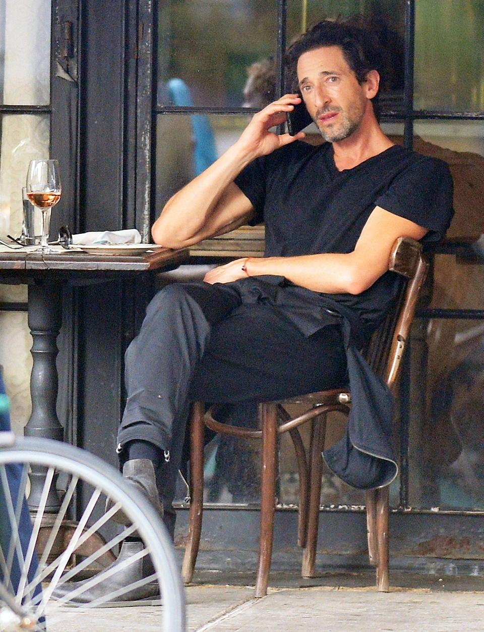 <p>An incognito Adrien Brody chats on his phone while enjoying a glass of wine outside at a New York City restaurant on Tuesday.</p>