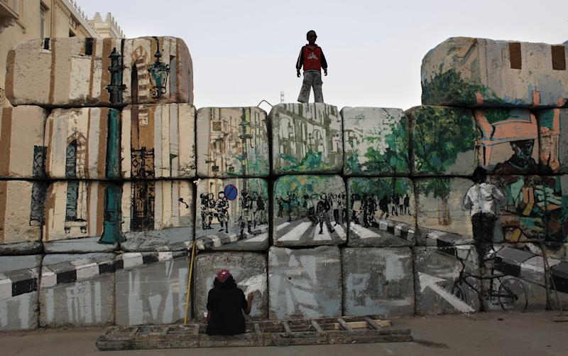 """In this Tuesday, March 13, 2012 photo, a boy watches an Egyptian female artist and activist at work on the """"No Walls Street"""" during the graffiti campaign to paint a reproduction of the streets behind them and targeted the concrete blocks walls in downtown Cairo, Egypt. After Egypt's ruling military sealed off streets around Cairo's Tahrir Square with walls of imposing concrete blocks, a group of artists decided to reopen the avenues on their own, in the public imagination, at least. (AP Photo/Nasser Nasser)"""