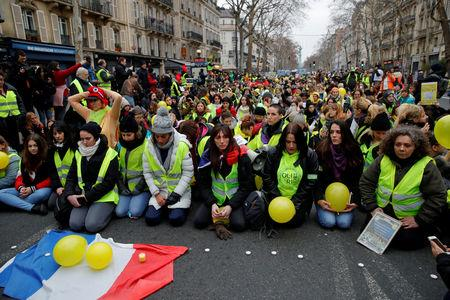 FILE PHOTO: Protesters wearing yellow vests kneel on the street as they take part in a demonstration in Paris, France, January 6, 2019.  REUTERS/Gonzalo Fuentes/File Photo