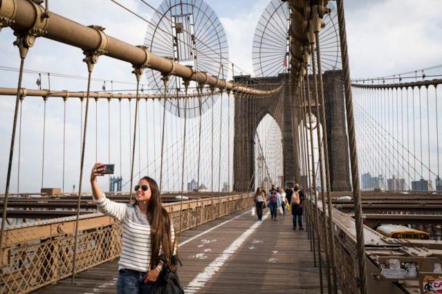 Tourists take photographs on the Brooklyn Bridge, March 1, 2017 in New York City.