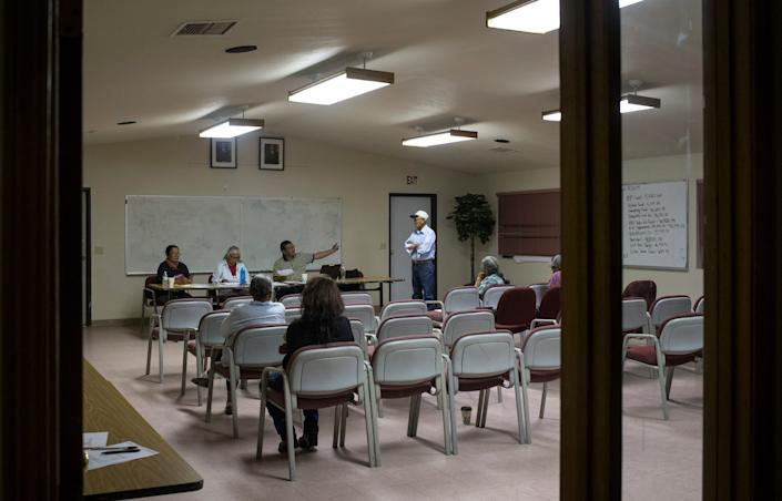 Jerry Williams (sitting right, president) talks with Wilson Lister Sr. (standing) during the LeChee Chapter Planning Meeting on Sept. 5, 2019, in LeChee, Arizona.