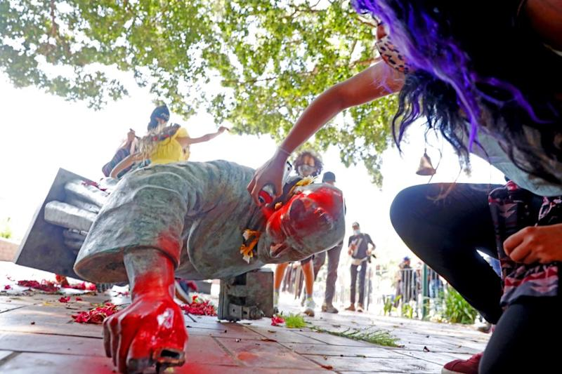 LOS ANGELES, CA - JUNE 20: Activists topple and deface with red paint the statue of Father Junipero Serra (1713 - 1784) at Father Serra Park in Pueblo Amigo on Saturday, June 20, 2020 in Los Angeles, CA. Junipero Serra, a Roman Catholic Spanish priest, who found the first nine of 21 Spanish missions in California from San Diego to San Francisco, in what was then Alta California in the Province of Las Californias, New Spain. (Gary Coronado / Los Angeles Times)