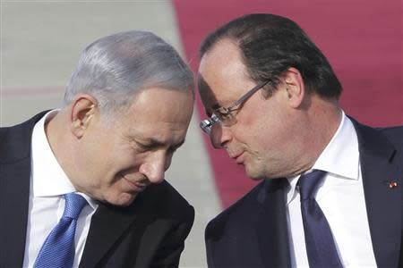 French President Francois Hollande listens to Israel's Prime Minister Benjamin Netanyahu (L) during his welcome ceremony at Jerusalem's Ben Gourion airport for a tree-days state visit, November 17, 2013. Israeli Prime Minister Benjamin Netanyahu pressed France on Friday not to weaken in its stance toward Iran in upcoming talks on the Islamic state's nuclear programme REUTERS/Philippe Wojazer