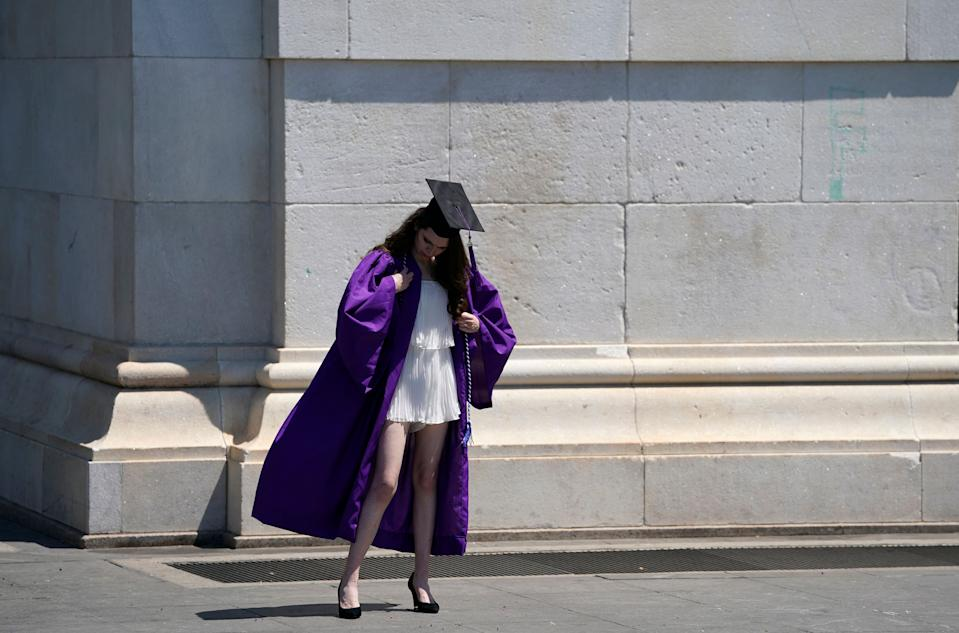 A graduate fixes her outfit before getting her picture taken in Washington Square Park, New York on May 19, 2021. (Photo by TIMOTHY A. CLARY / AFP)