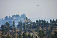 In this photo provided by the Bureau of Land Management, a helicopter works above the Devil's Creek Fire in central Montana on Thursday, July 22, 2021. Five firefighters were injured when a thunderstorm and swirling winds in central Montana blew a lightning-caused wildfire back on them, federal officials said Friday, July 23, 2021. (Mark Jacobsen/Bureau of Land Management via AP)
