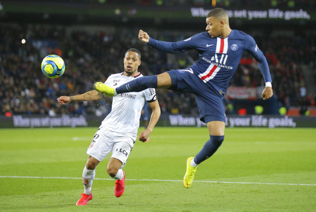 Dijon's Mickael Alphonse, left, and PSG's Kylian Mbappe challenge for the ball during the French League One soccer match between Paris-Saint-Germain and Dijon, at the Parc des Princes stadium in Paris, France, Saturday, Feb. 29, 2020. (AP Photo/Michel Euler)