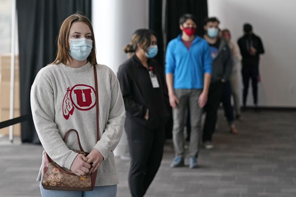 University of Utah student Abigail Shull waits in line before taking a rapid COVID-19 test at the University of Utah student testing site Wednesday, Nov. 18, 2020, in Salt Lake City. As college students prepare to go home for the holidays, some schools are quickly ramping up COVID-19 testing to try to keep infections from spreading further as the coronavirus surges across the U.S. (AP Photo/Rick Bowmer)