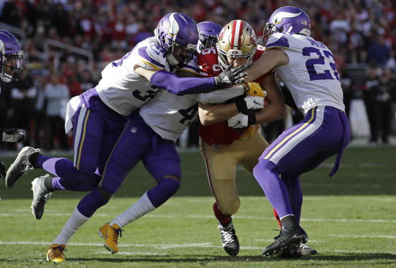 San Francisco 49ers tight end George Kittle, center, is tackled by Minnesota Vikings Minnesota Vikings free safety Harrison Smith, right, and other defenders during the first half of an NFL divisional playoff football game, Saturday, Jan. 11, 2020, in Santa Clara, Calif. (AP Photo/Marcio Jose Sanchez)