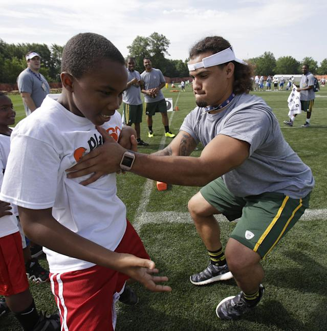 Green Bay Packers' Carl Bradford, right, blocks a a participant during an NFL football Play 60 youth event at the Cleveland Browns practice facility Tuesday, June 24, 2014, in Berea, Ohio. The NFC rookies took part in the NFL's annual Rookie Symposium. (AP Photo/Tony Dejak)