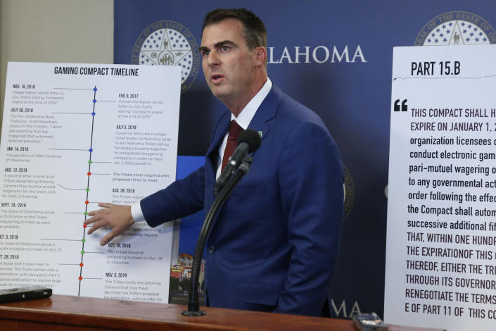 Oklahoma Gov. Kevin Stitt gestures to a sign concerning the renewal of Tribal Gaming Compacts during a news conference Thursday, Nov. 14, 2019, in Oklahoma City. (AP Photo/Sue Ogrocki)